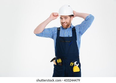 Portrait of happy bearded young builder in overall and helmet