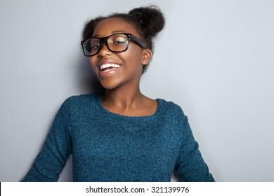 Portrait of happy beautiful african young girl with toothy smile. Teenage girl posing in studio, wearing fashionable eyeglasses.