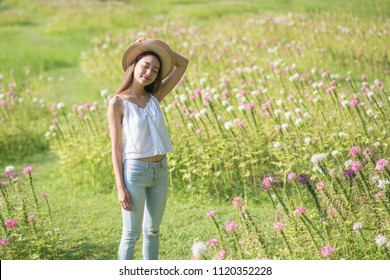 Portrait of Happy beautiful Asian woman with hat relax at grass field with pink flowers in morning. Outdoor lifestyle. Freedom concept. Brunette woman get fresh air in summer park.