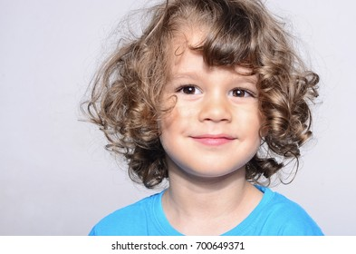 Portrait of a happy beautiful boy. Toddler smiling and having fun.  Kid making funny faces. Boy with long curly hair.