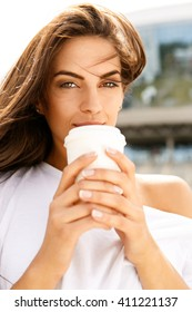 Portrait of happy beautiful brunette girl with long healthy hair in front of business sport building hold with two hands paper cup with hot coffee tea and look to the camera. Urban scene, city life.