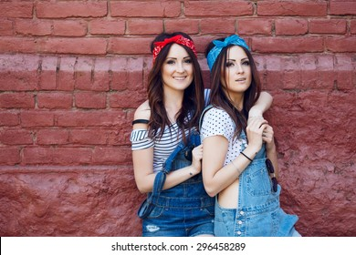 Portrait of happy beautiful brunette twins girls, with long dark-brown straight hair. Hugging front of the urban wall background. Wearing denim overalls, bright bandanas and white top, posing outdoors