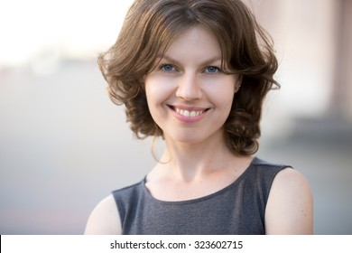 Portrait of happy beautiful business woman posing on the street in summer, friendly smiling, looking at camera with cheerful confident expression