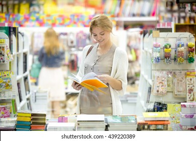 Portrait of happy beautiful caucasian person standing in bookstore and looking through books with a smile. Young smiling model wearing casual clothing choosing book in outlet during shopping time