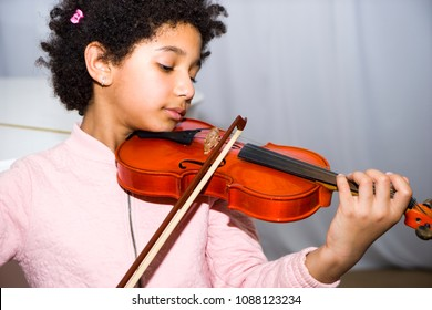 Portrait of happy beautiful dark skinned little girl using a violin while playing a melody