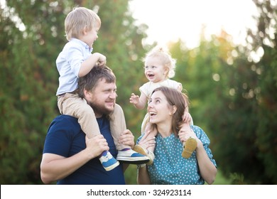 Portrait of happy beautiful family of four walking in park in summer. Mom and dad carrying two little cheerful laughing kids on shoulders. Parents and siblings playing, having fun together