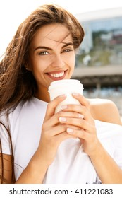 Portrait of happy beautiful girl with long healthy hair in front of business sport building hold with two hands paper cup with hot coffee tea look to the camera and smile. Urban scene, city life.