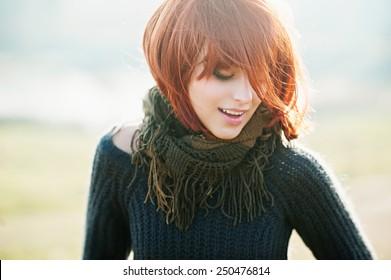 Porträt eines glücklichen schönen Mädchens mit roten Haaren auf dem Feld, Lifestyle
