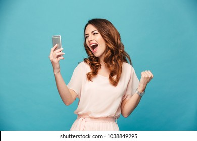 Portrait of a happy beautiful girl wearing dress looking at mobile phone and celebrating isolated over blue background