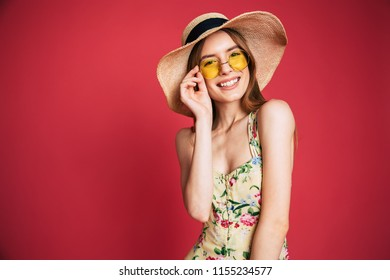 Portrait of happy beautiful lovely young blonde woman in sunglasses is have a fun while posing on pink background