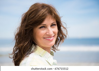 Portrait of a happy and beautiful middle aged woman on the beach