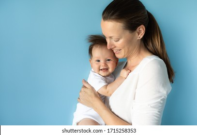 Portrait of happy beautiful mother holding her cute baby girl against blue studio background. Mothers Day, family, and parenting concept.