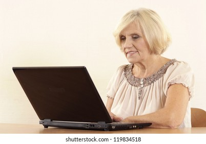 portrait of happy beautiful old woman with a laptop