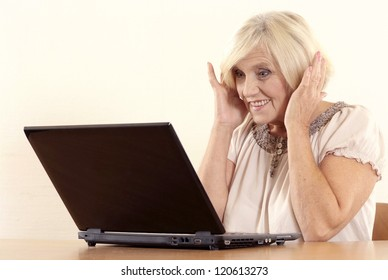 portrait of happy beautiful old woman with a laptop on a beige