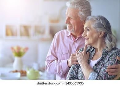 Porträt eines glücklichen, schönen Seniorenpaar, das zu Hause posiert