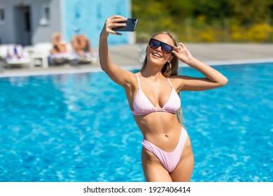 Portrait of a happy beautiful woman in bikini and sunglasses making selfie photo on smartphone outdoors