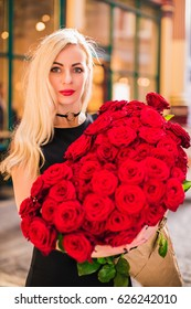 Portrait of happy beautiful woman who stands and keeps big bouquet of red roses in hands, on the street