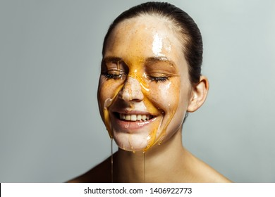 Portrait of happy beautiful young brunette woman with freckles and honey on face with closed eyes and toothy smile happiness face. indoor studio shot isolated on gray background.