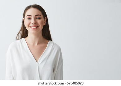 Portrait of happy beautiful young businesswoman smiling looking at camera over white background.