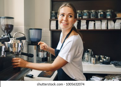 Portrait of happy beautiful young Caucasian smiling woman barista holding plastic cup with ice. Server making cold drink in coffee shop. Small business owner and person at work concept.