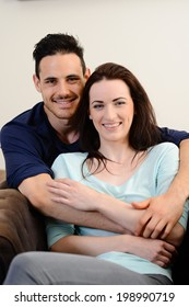 portrait of happy beautiful young couple relaxing on sofa together at home