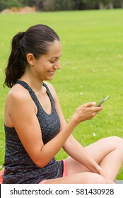Portrait happy beautiful young hispanic woman relaxed using smart phone, networking, texting, chatting in park outdoor after exercising, blurred background.