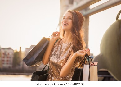 Portrait of the happy beautiful young woman who is standing outdoors and holding the shopping bags in hands