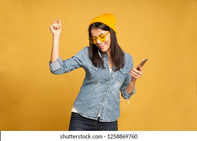 Portrait of happy beautiful young woman listening music on her phone, dancing and smiling, wearing denim shirt, yellow hat and yellow glasses, isolated on yellow background