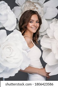 Portrait of happy beautiful young woman surrounded by white flower decorations