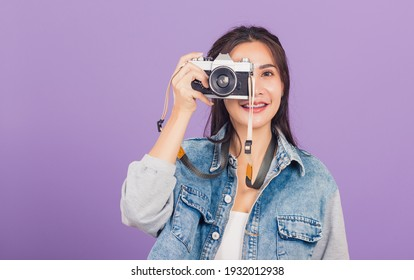 Portrait happy beautiful young woman smile excited wear denims photographer taking a picture and looking viewfinder on vintage photo camera ready to shoot, studio shot isolated on purple background