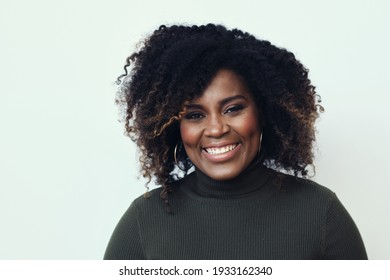 Portrait of happy beautiful young woman with curly hair green sweater against white background