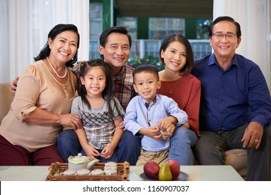 Portrait of happy big Vietnamese family sitting on sofa and smiling at camera