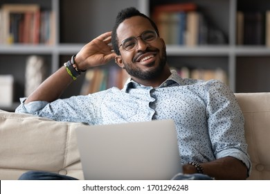 Portrait of happy biracial young man in glasses sit rest on couch at home working on laptop, smiling African American millennial male relax on sofa in living room browsing Internet on modern computer