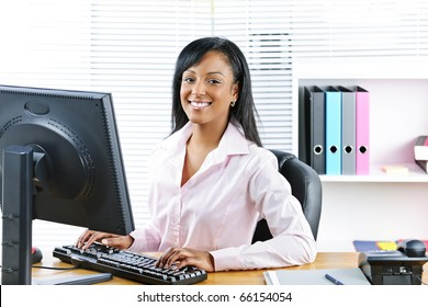 Portrait of happy black business woman at desk typing on computer