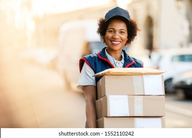 Portrait of happy black courier delivering packages and looking at the camera.