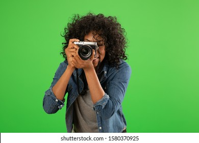 Portrait of happy black female photographer taking a photo. Young pretty woman shooting with camera on greenscreen