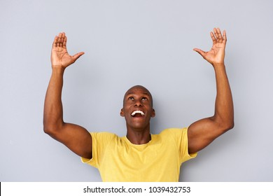 Portrait of happy black man with arms and hands raised to lift