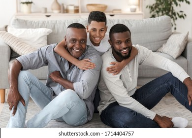 Portrait of happy black multi generation family at home. Son, father and grandfather posing indoors in living room, hugging and smiling