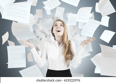 Portrait of a happy blond businesswoman throwing papers in the air and laughing. Concept of a work well done