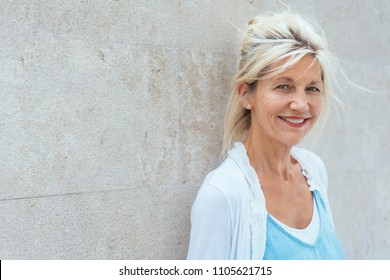 A portrait of happy, blond haired, mature woman smiling at camera while leaning on a wall.