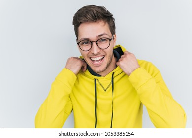 Portrait of happy blond wears yellow hoody and trendy glasses looks cheerful confidently into camera. Young smiling student man posing against white studio wall. People, lifestyle and emotion concept