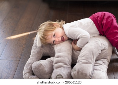 portrait of happy blonde caucasian baby nineteen month age looking at camera smiling  face embraced grey plush doll on brown wooden floor