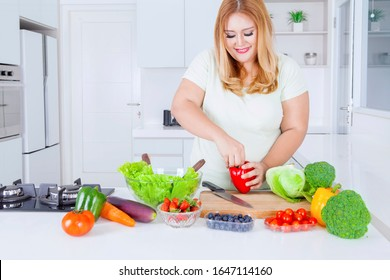 Portrait of happy blonde overweight woman preparing fresh vegetable to make salad in the kitchen at home