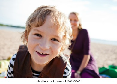 Portrait of a happy boy at the beach with his mother in the background.