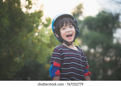 Portrait of happy Boy in blue helmet standing with nature background