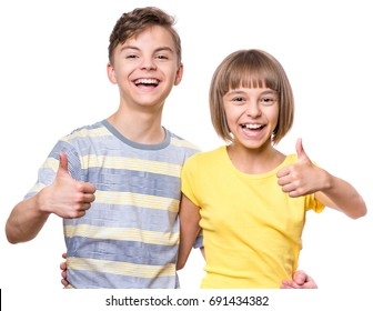 Portrait of happy boy and girl showing thumbs up gesture. Cute brother and sister isolated on white background. Funny couple children laughing with a perfect smile.