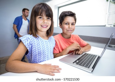 Portrait of happy boy and girl using laptop in their living room