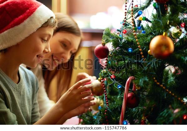 Portrait of happy boy in Santa cap decorating Christmas tree