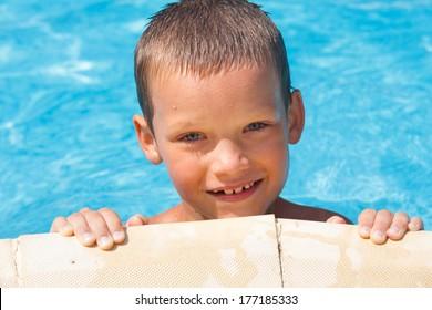 Portrait happy boy in the summer outdoor pool.