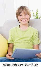 Portrait of happy boy using digital tablet on sofa at home